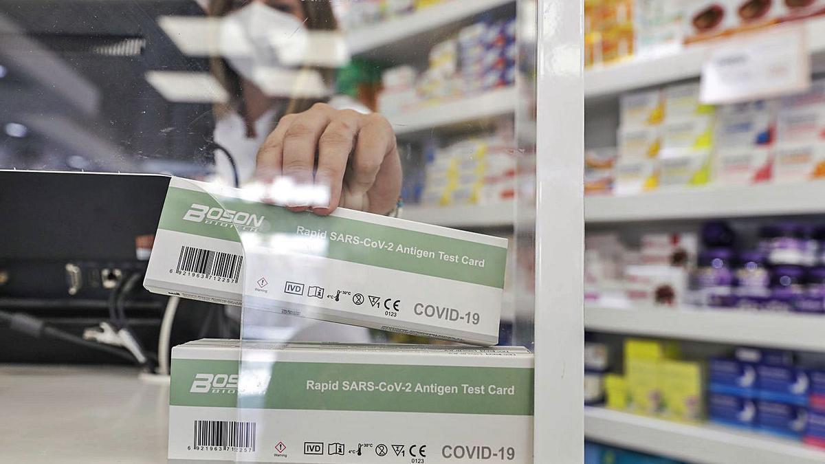 Una farmacéutica se dispone a dispensar un test de antígenos en una farmacia.