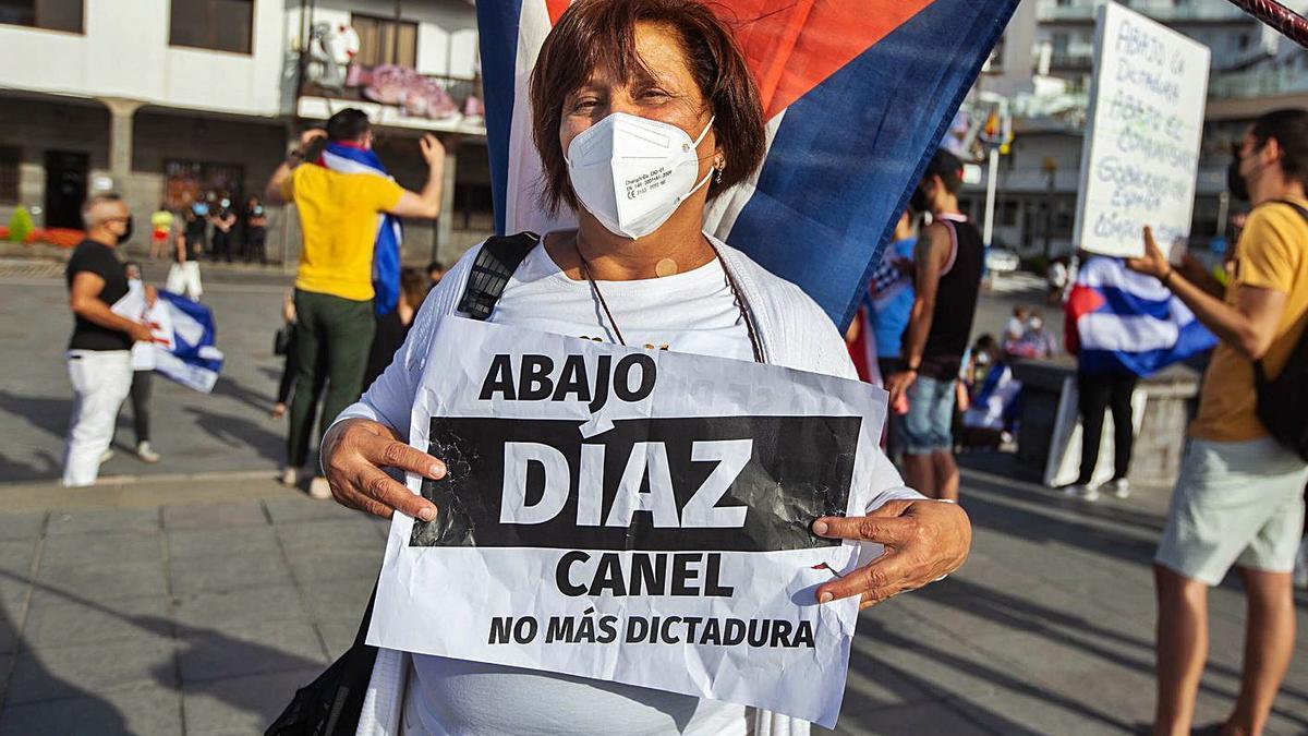 Miguelina con un cartel contra el actual presidente de Cuba, Miguel Díaz-Canel. | | CARSTEN W. LAURITSEN