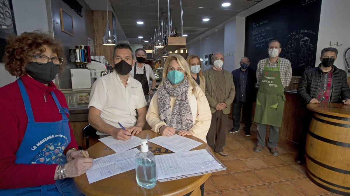 Vecinos y comerciantes de La Roqueta, en el bar Marzal, firman contra el Chinatown en Pelayo.