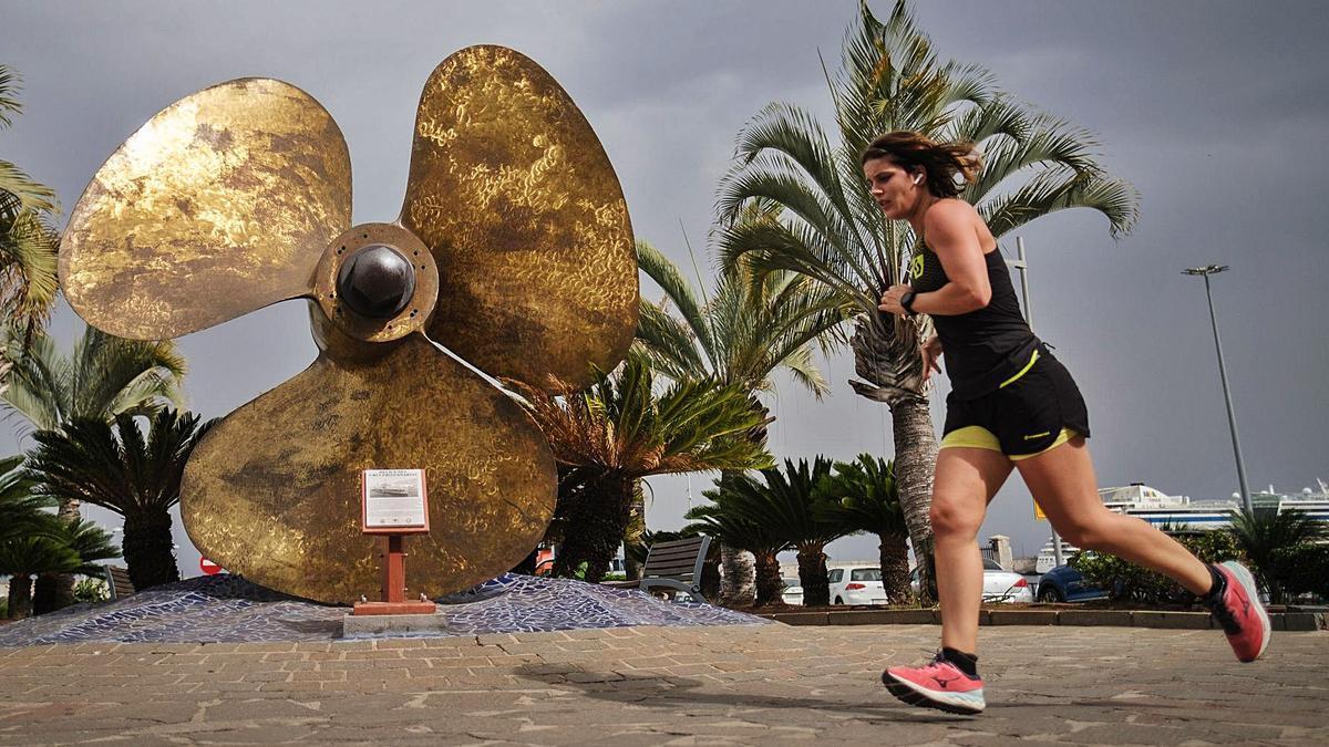 Una mujer corre junto a la hélice del crucero 'Canarias', a la entrada del Muelle Norte de Santa Cruz.     ANDRÉS GUTIÉRREZ