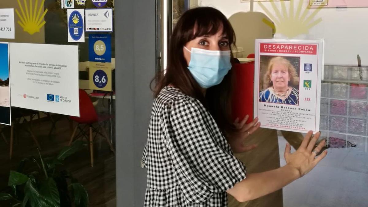 Raquel Álvarez, hija de la mujer desaparecida, coloca un cartel en un albergue de peregrinos.   // FdV
