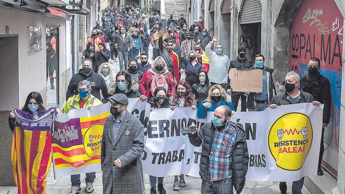 Manifestantes brazo en alto a su paso por el centro de Palma.