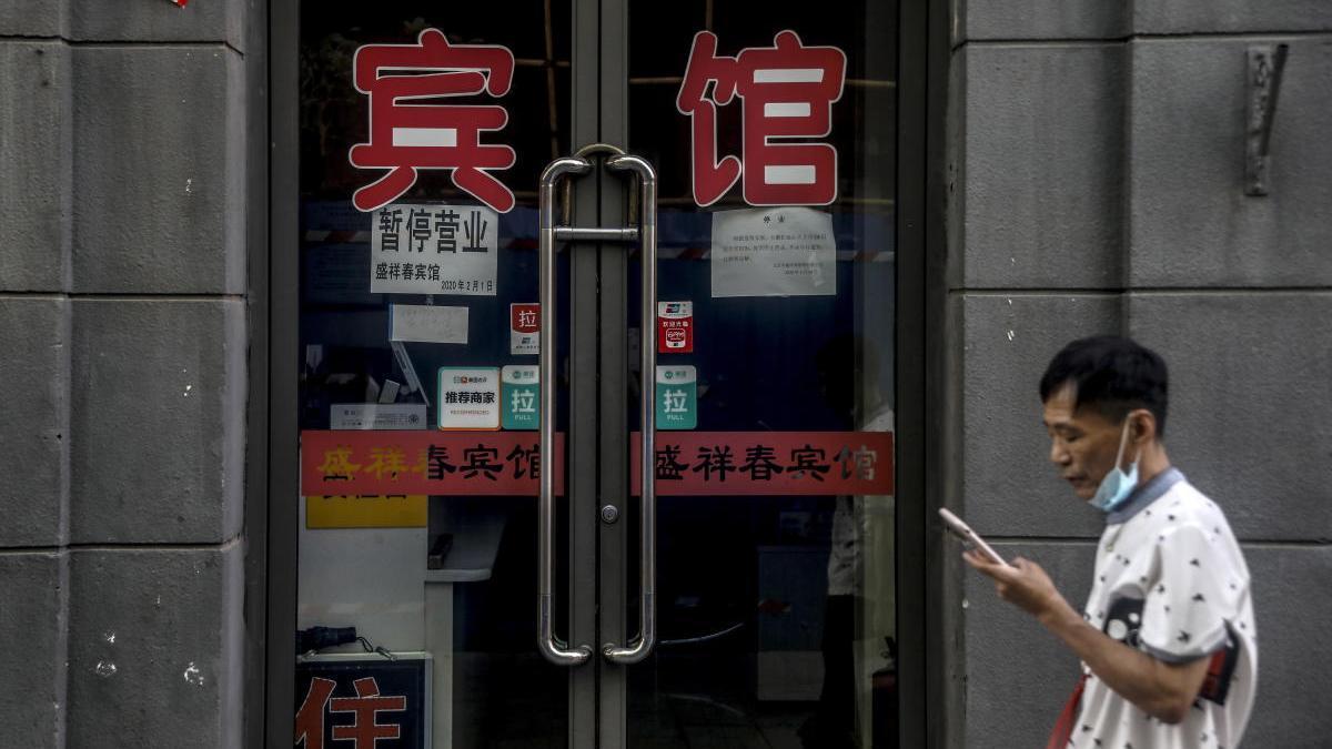 Un hombre pasa por delante de un comercio cerrado en China por el coronavirus.