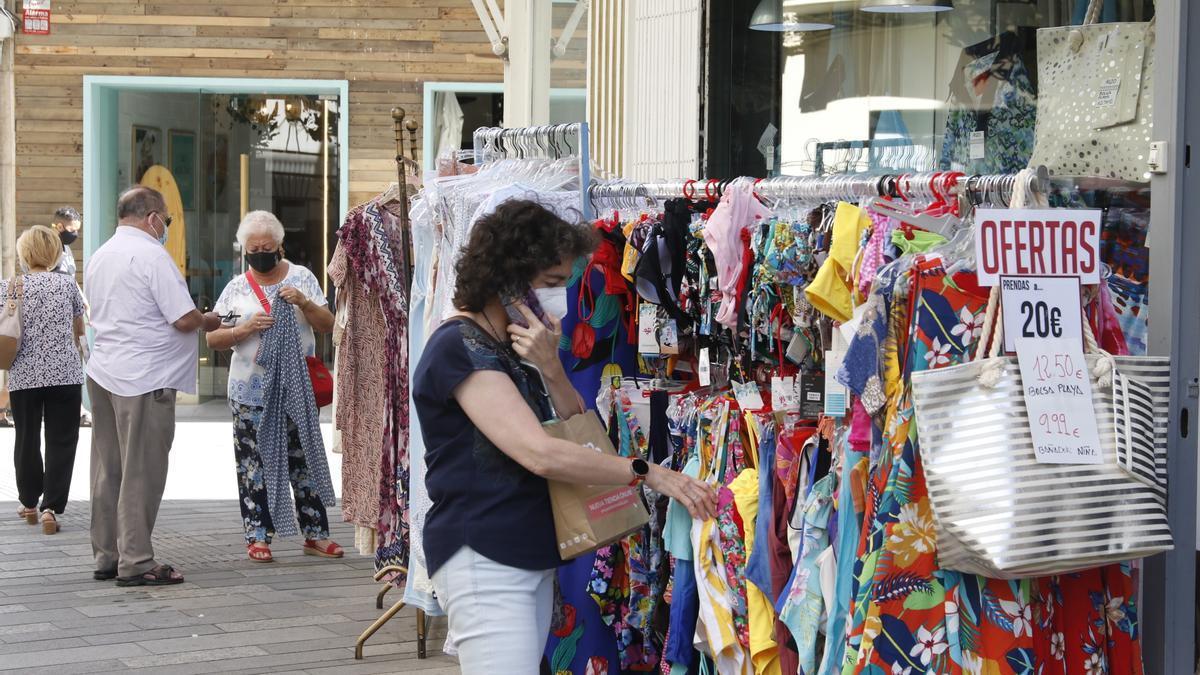 Varios clientes observan prendas de ropa a las puertas de un comercio.
