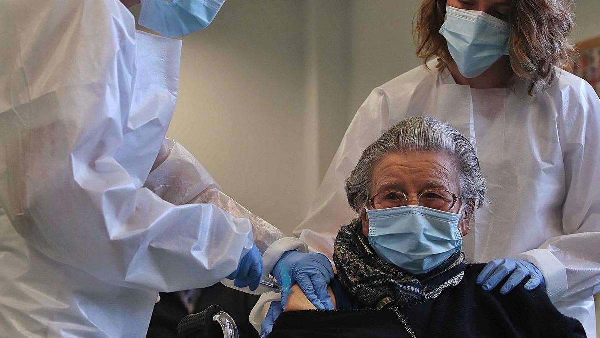 Dos enfermeras vacunan a una mujer de más de 80 años en el centro de salud de Burjassot.  | J. M. LÓPEZ
