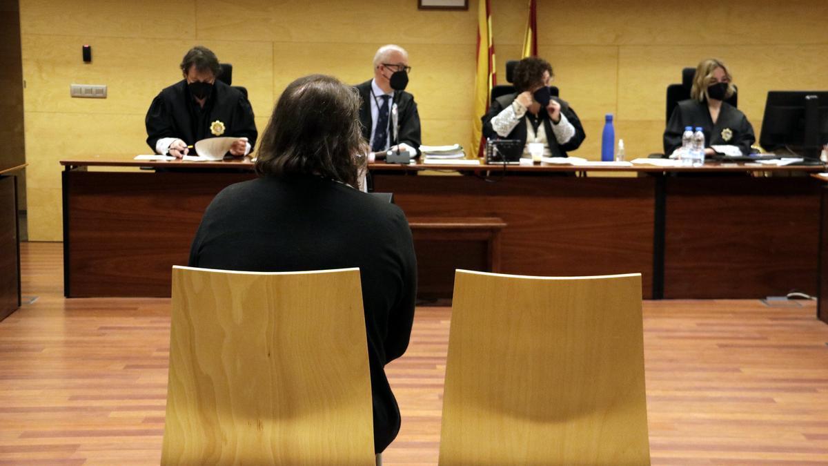 D'esquenes, l'acusada de donar una propietat al fill per evitar que la Seguretat Social li embargués. Foto del judici a l'Audiència de Girona el 17 de maig del 2021 (horitzontal)