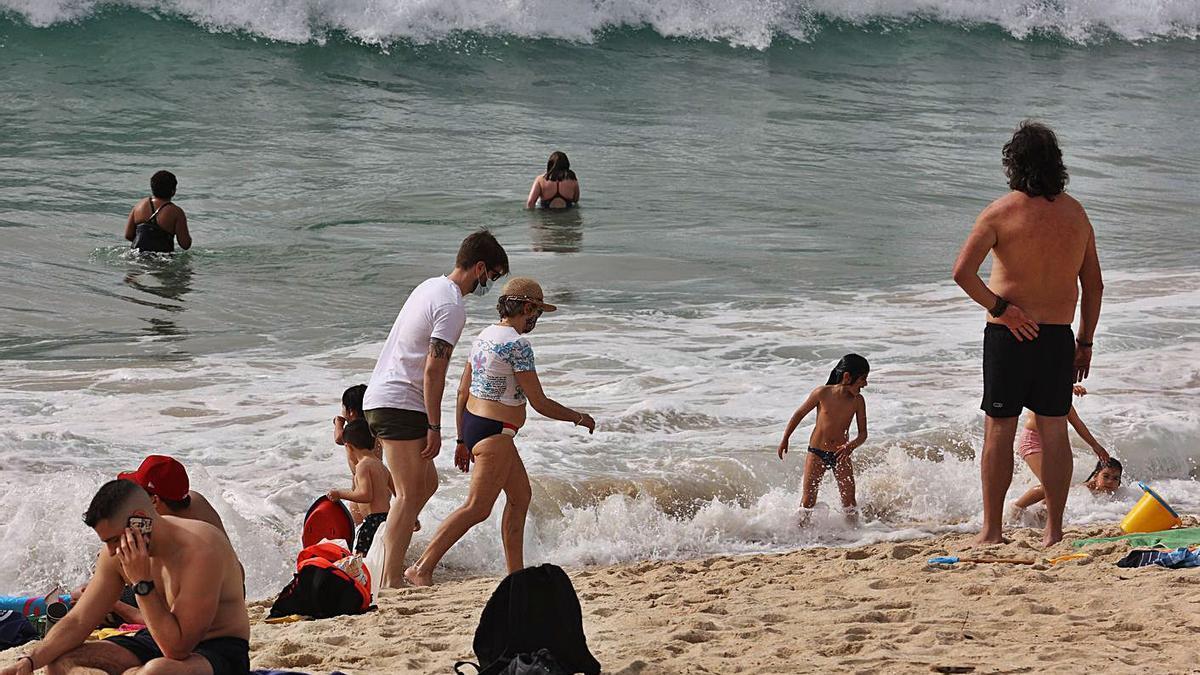 Bañistas en Samil, donde llevan mascarilla los que pasean por la orilla.     // ALBA VILLAR