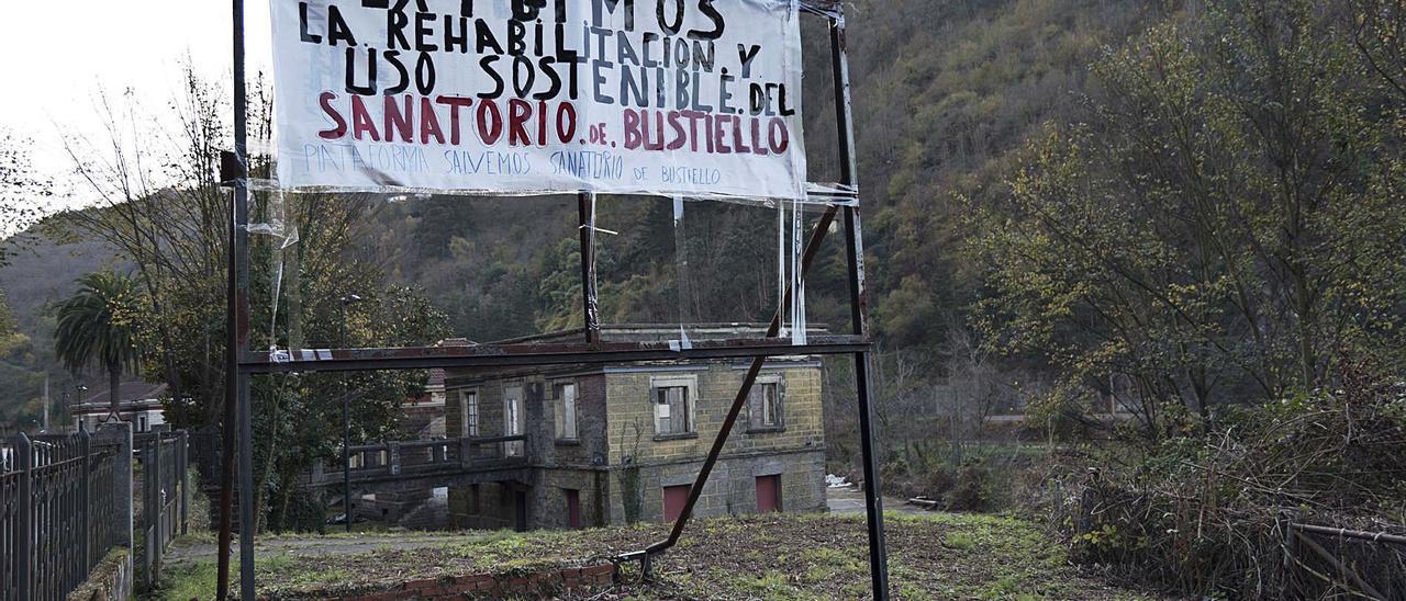 Una pancarta de protesta, con el edificio de la botica justo detrás. | Jandro Rodríguez