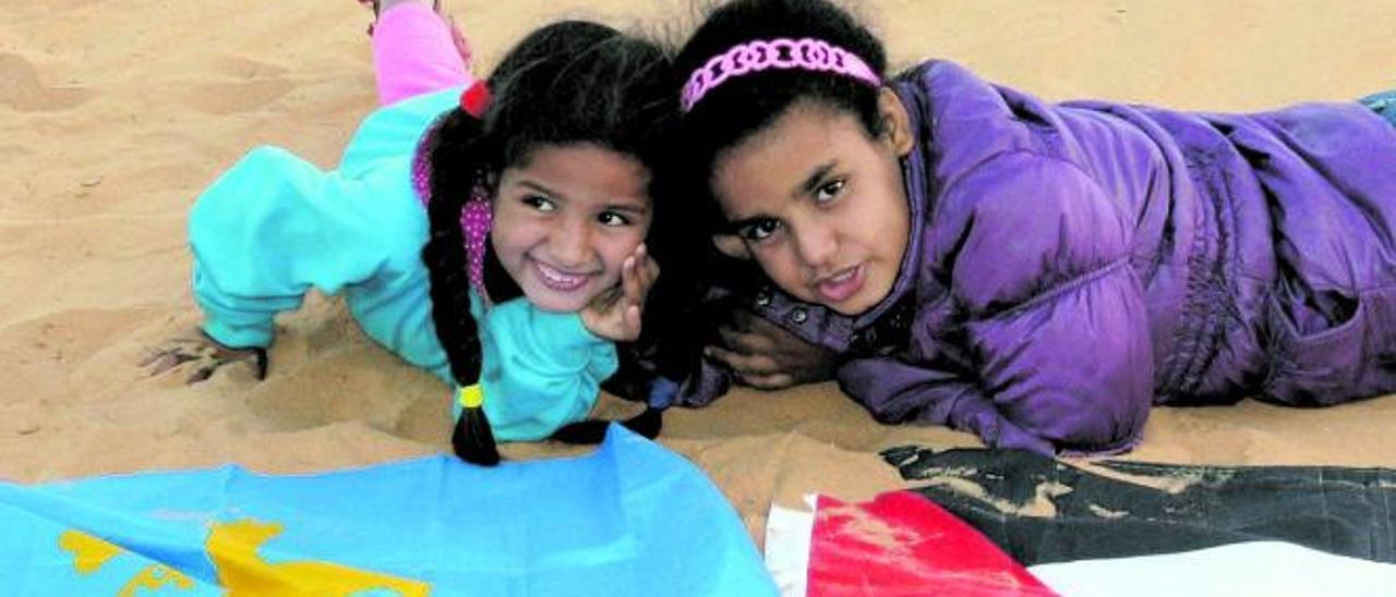 Glana y Aziza Fadil, con las banderas del Sahara y de Asturias, en el campamento de Dajla