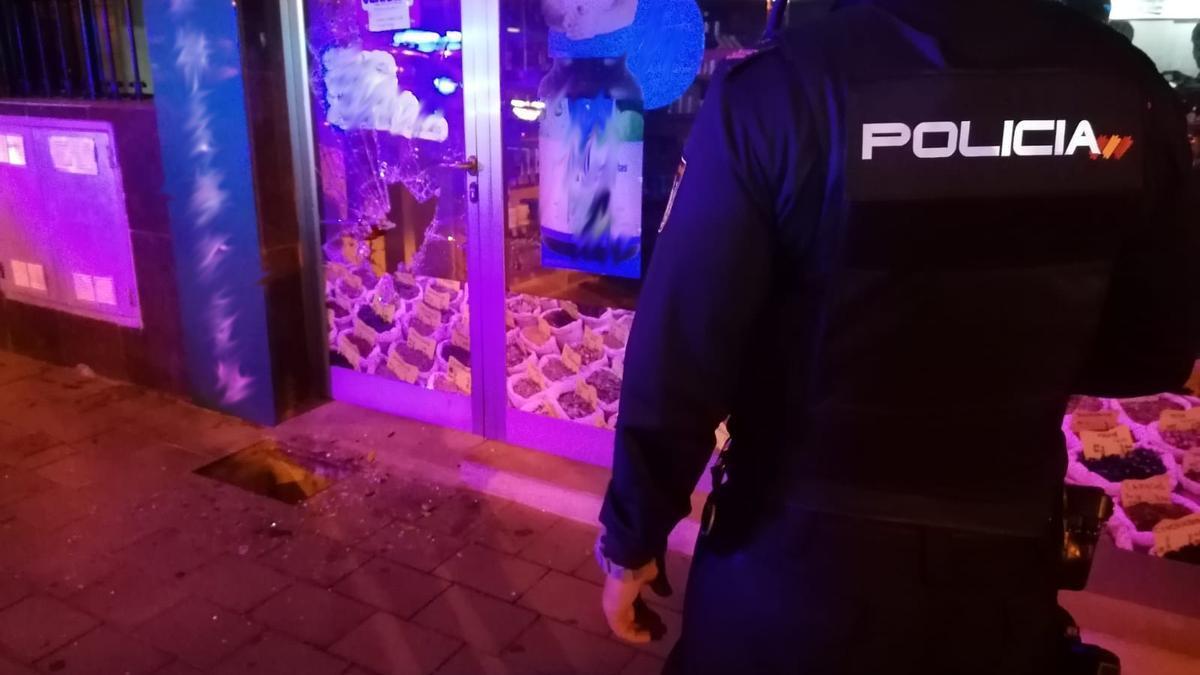 Un policía observa la puerta del comercio, con un agujero en el cristal.