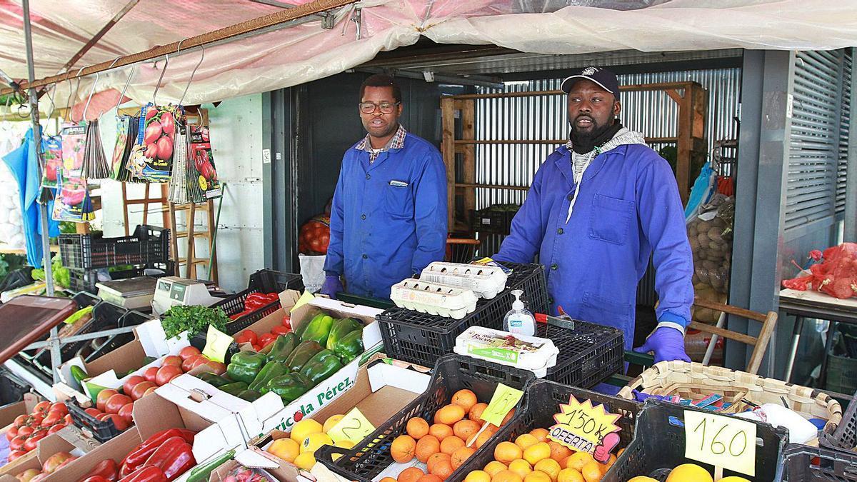 Ibrahim y Baye, senegaleses, trabajando en el rianxo de la plaza de abastos de Ourense.     // IÑAKI OSORIO