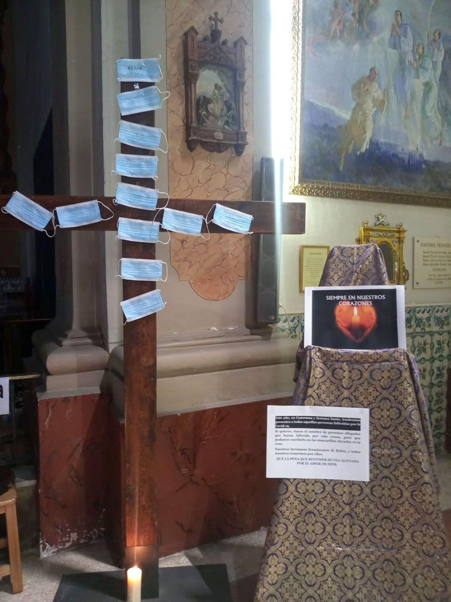Clavan mascarillas con nombres de fallecidos por covid sobre una cruz de madera en un convento de València