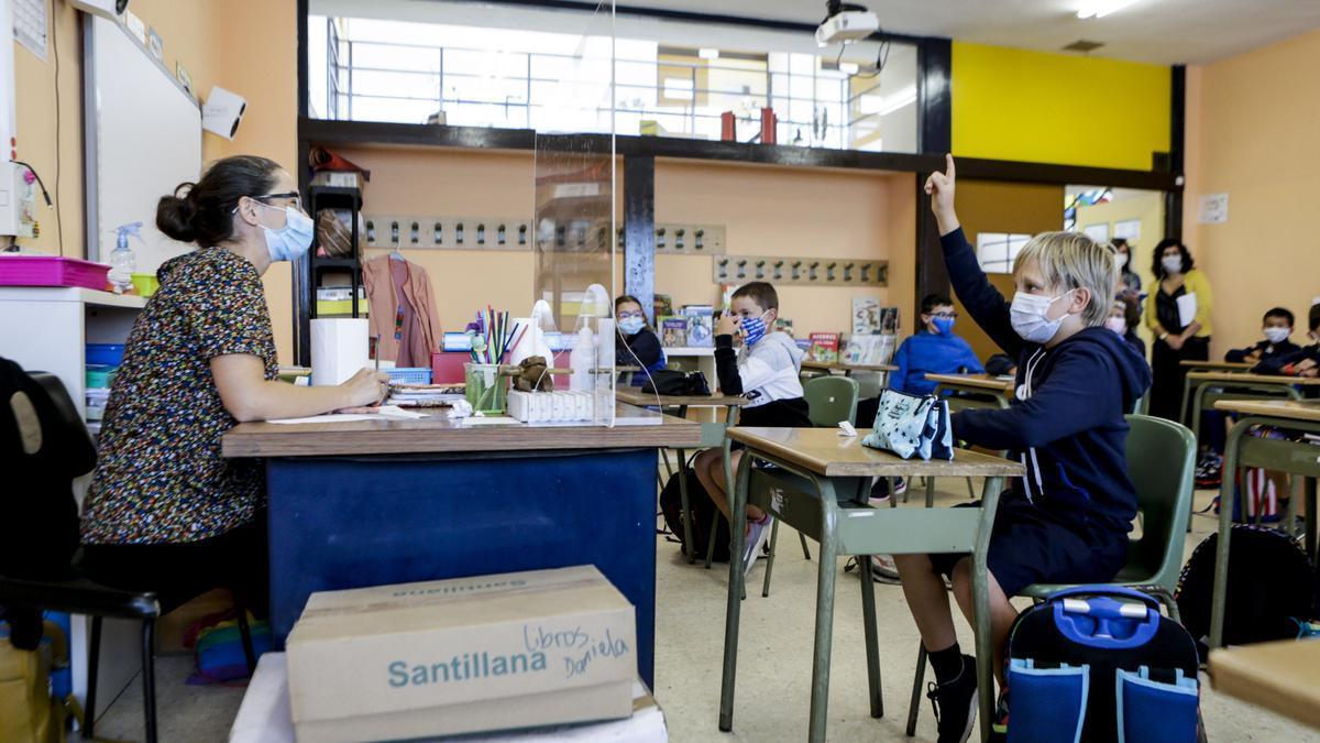 Profesores y alumnos usan mascarillas en una clase.