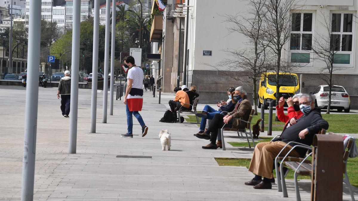 Ciudadanos en un área peatonal de la Marina de A Coruña.