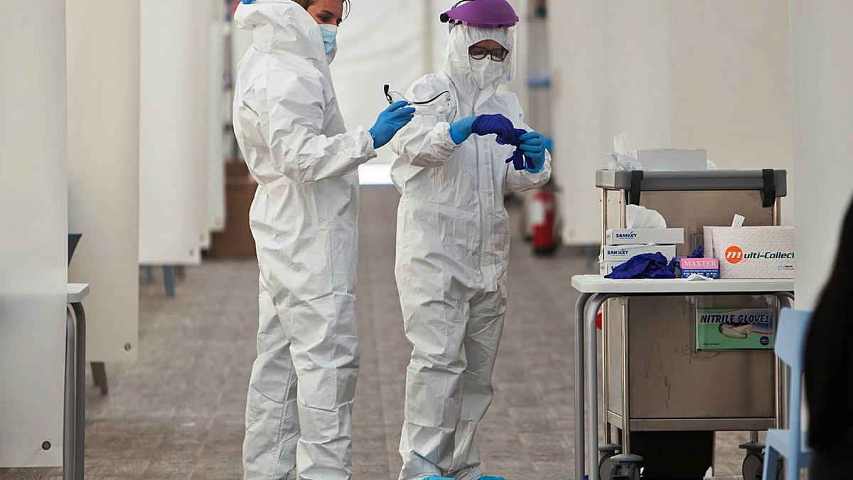 Dos sanitarias se preparan para realizar PCR a pacientes en el hospital de campaña de La Fe.  | GERMÁN CABALLERO