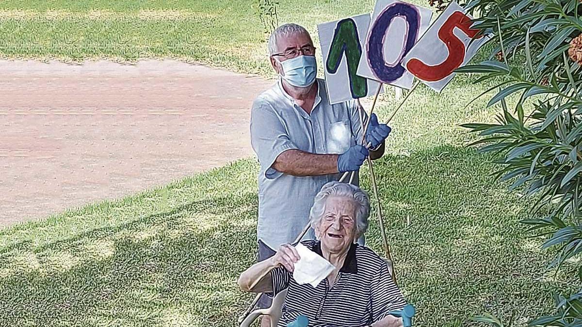 Francisca Pizà, junto a su hijo, Vicenç, en el jardín de la residencia, recibe las felicitaciones a distancia.