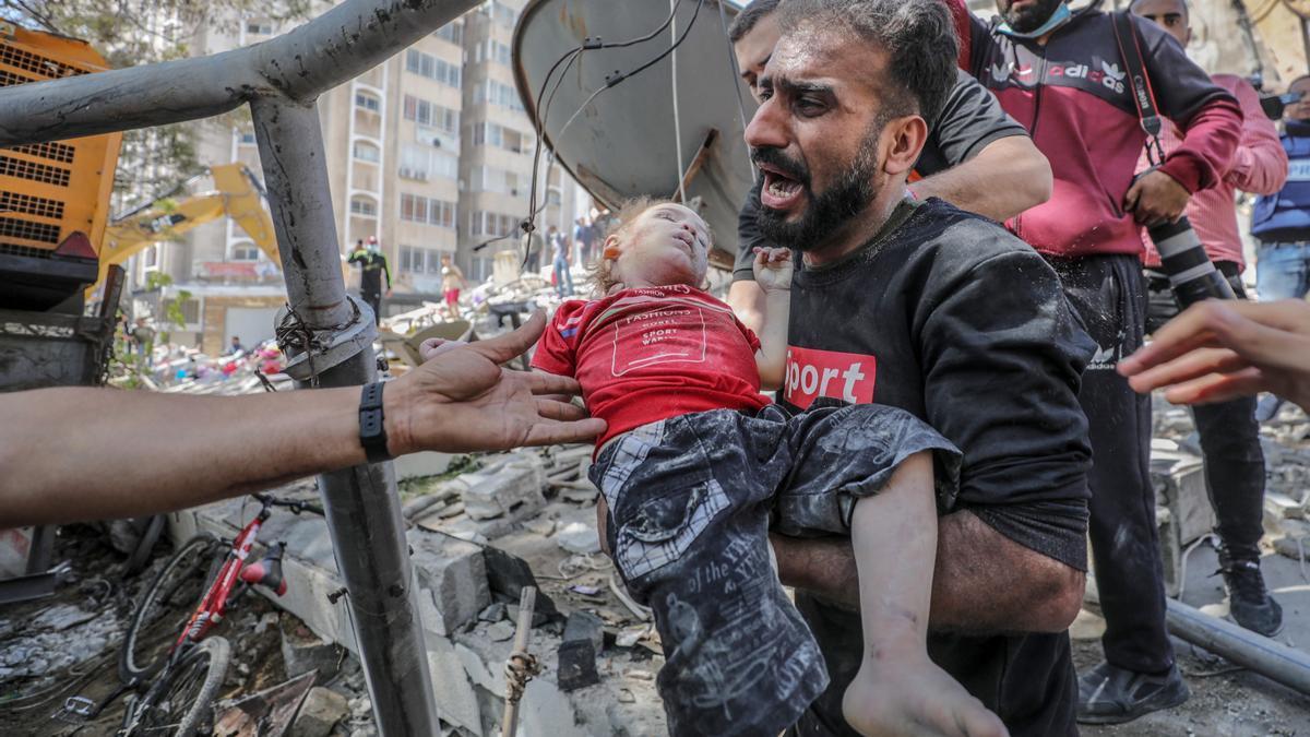 Un hombre porta el cuerpo de un niño herido tras uno de los bombardeos sobre Gaza.