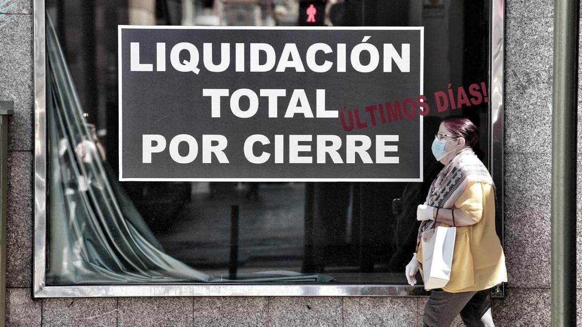 Una mujer pasa junto al escaparate de un comercio en liquidación.