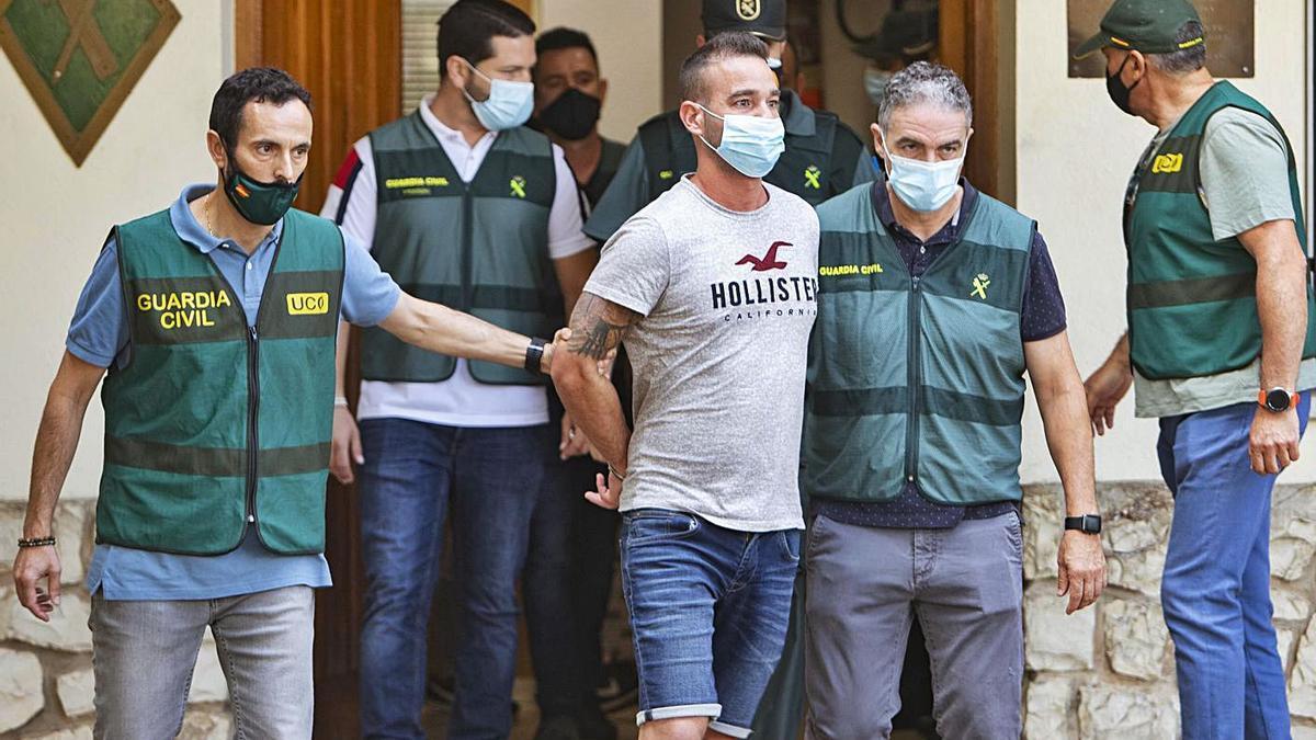 El presunto asesino, rodeado de los investigadores, de camino al registro de su casa. | PERALES IBORRA