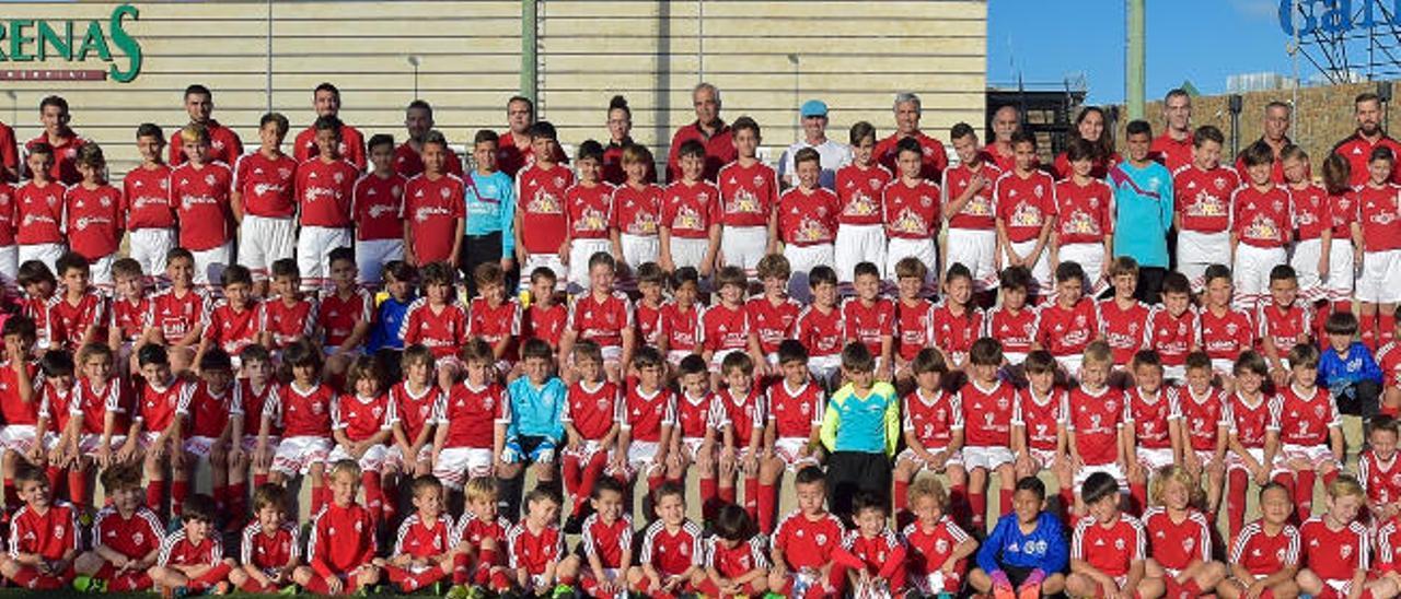 Foto de familia con los diferentes equipos de fútbol 8 de la cadena del Veteranos de Pilar en la pequeña grada del campo Manuel Naranjo Sosa 1.