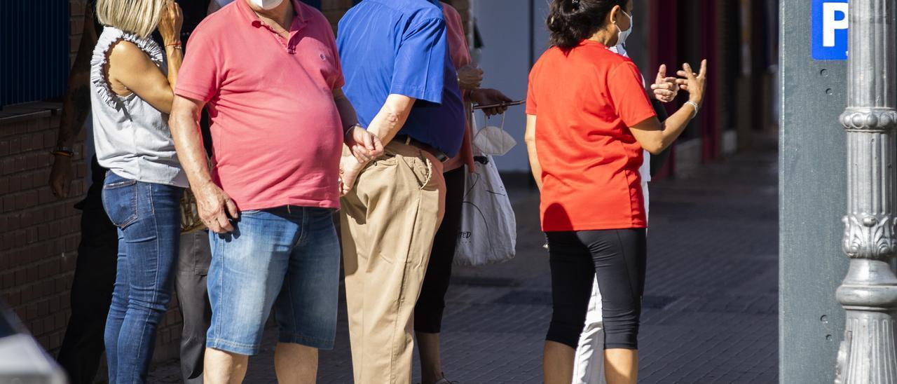 Un grupo de ciudadanos hace cola para pagar en un parquímetro de València ayer.