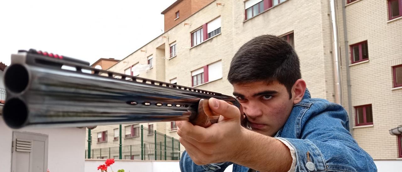 Samuel Cueva empuñando la escopeta en su casa de Noreña