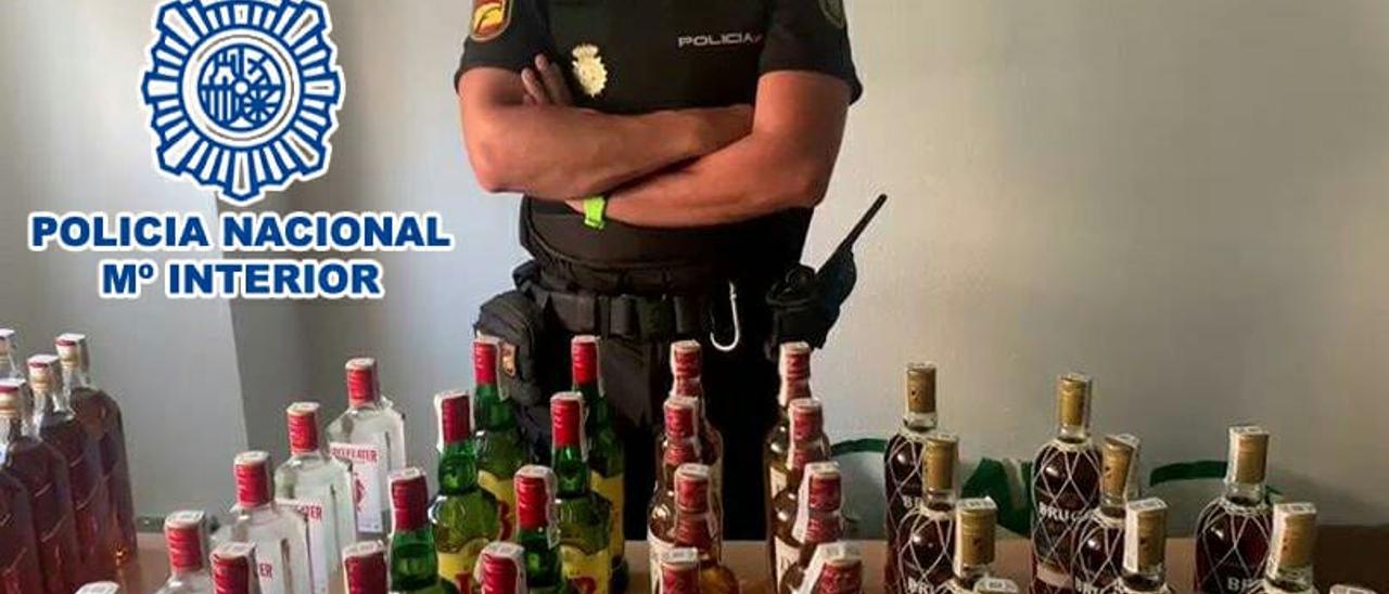 Un agente con las botellas recuperadas.
