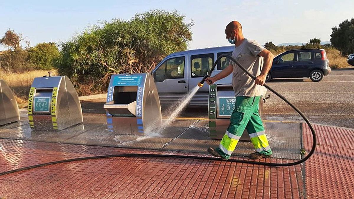 Un operario limpia el entorno de unos contenedores de basura en Formentera.