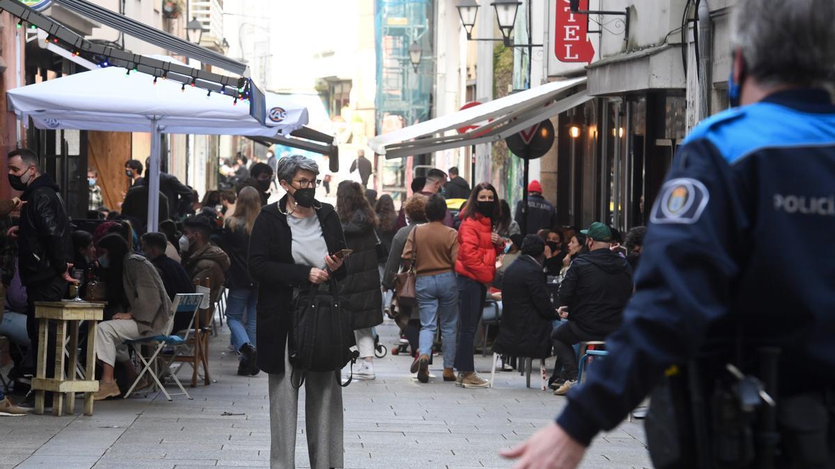 La policía vigila el cumplimiento de las medidas de seguridad en una zona de terrazas en A Coruña.