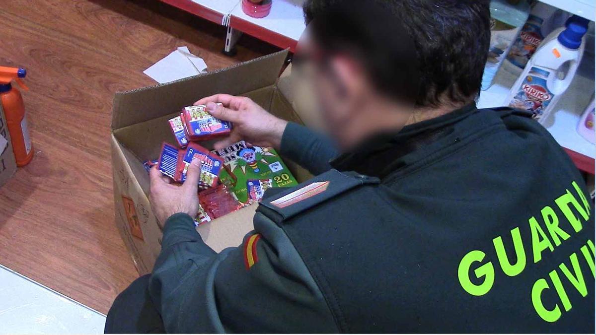 Un agente de la Guardia Civil examina artículos pirotécnicos en una tienda.