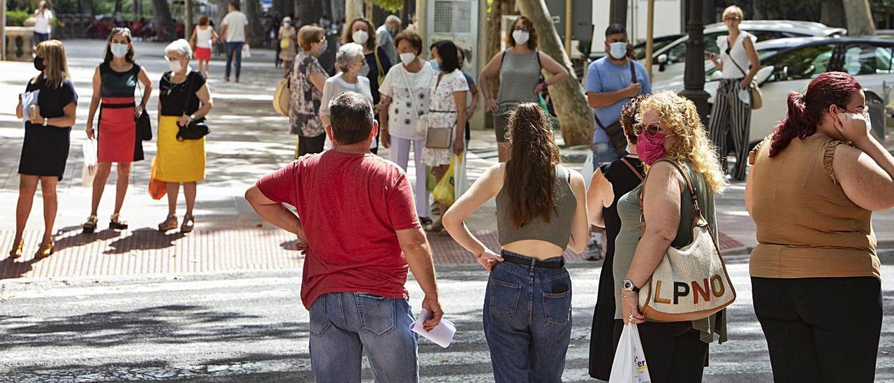 Vecinos de Xàtiva aguardan a cruzar una calle, en una fotografía de hace unos días | PERALES IBORRA