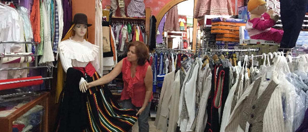 Josefa Rodríguez, conocida como Fefi, prepara, con la ropa típica canaria, uno de los maniquíes de su tienda Los Sombreritos en San Gregorio.