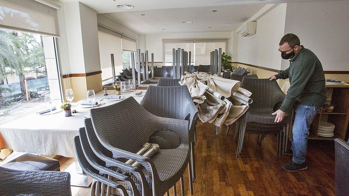 Apiladas mesas, sillas y sombrillas de veladores en un restaurante que podrá abrir su terraza.