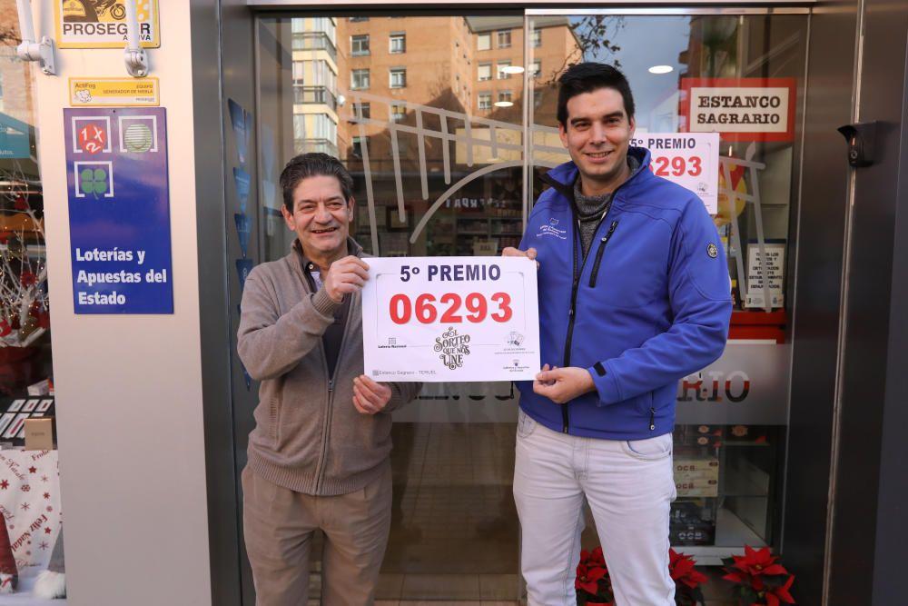 El delegado de de loterías de Teruel (i) y el lotero del estanco donde ha caído el premio (d)  posan con uno de los quintos premios de la Lotería de Navidad.