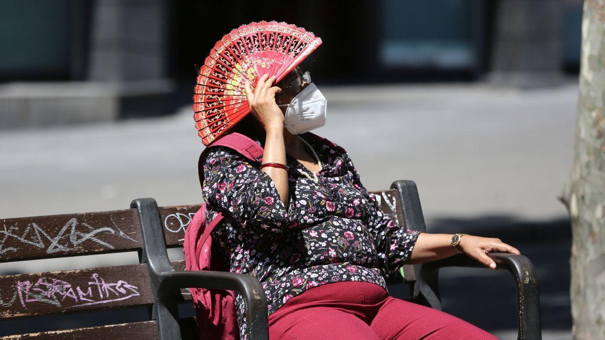 Una senyora es protegeix de el sol, davant l'onada de calor, a les Rambles de Barcelona.