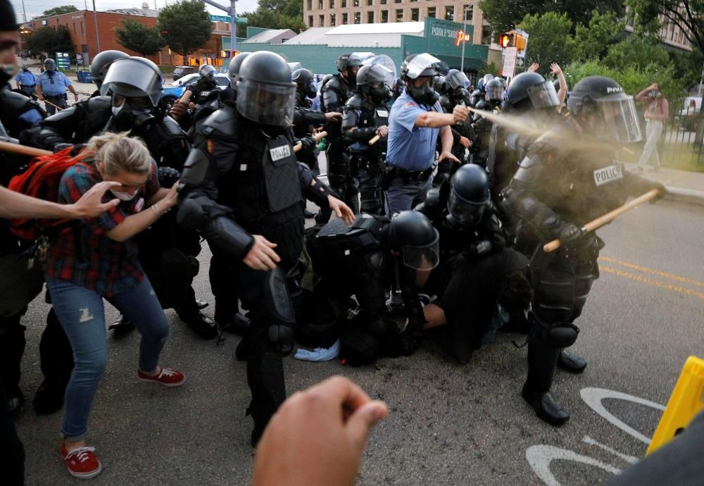 A policeman discharges pepper spray during ...