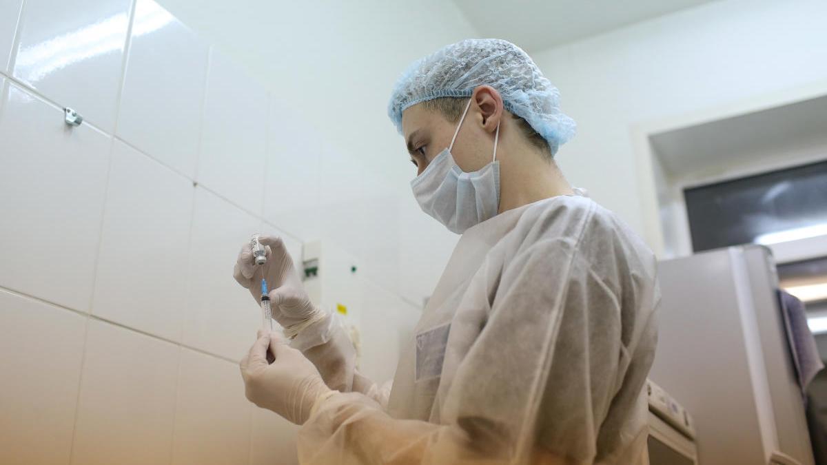 Un sanitario manipula una dosis de la vacuna rusa