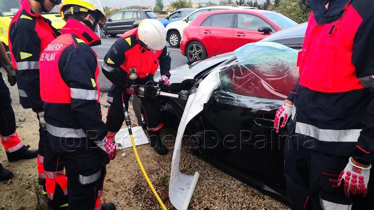 Los bomberos, durante el rescate de la mujer atrapada en su coche.