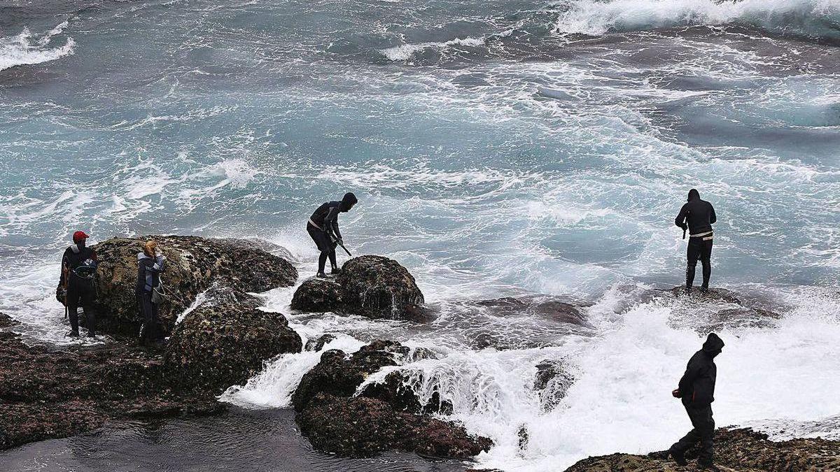 Un grupo de percebeiros de Baiona en plena faena con fuerte marejada.