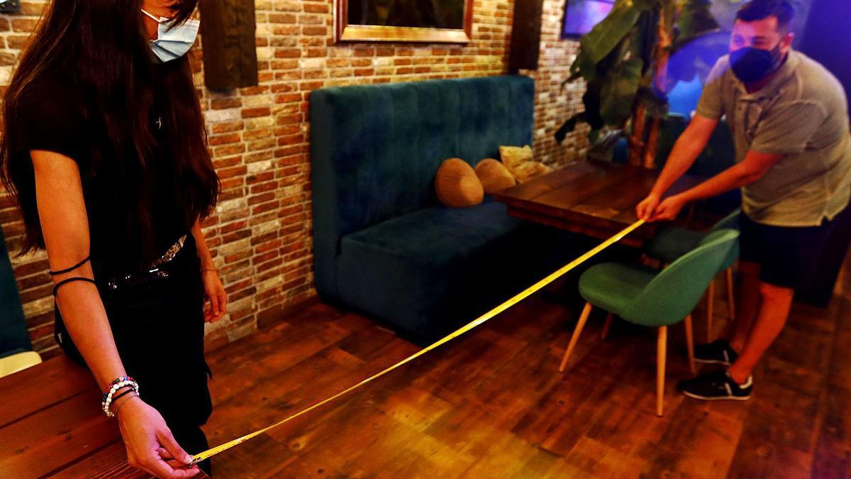 Dos empleados miden la distancia entre mesas en el gastro pub Bocachica