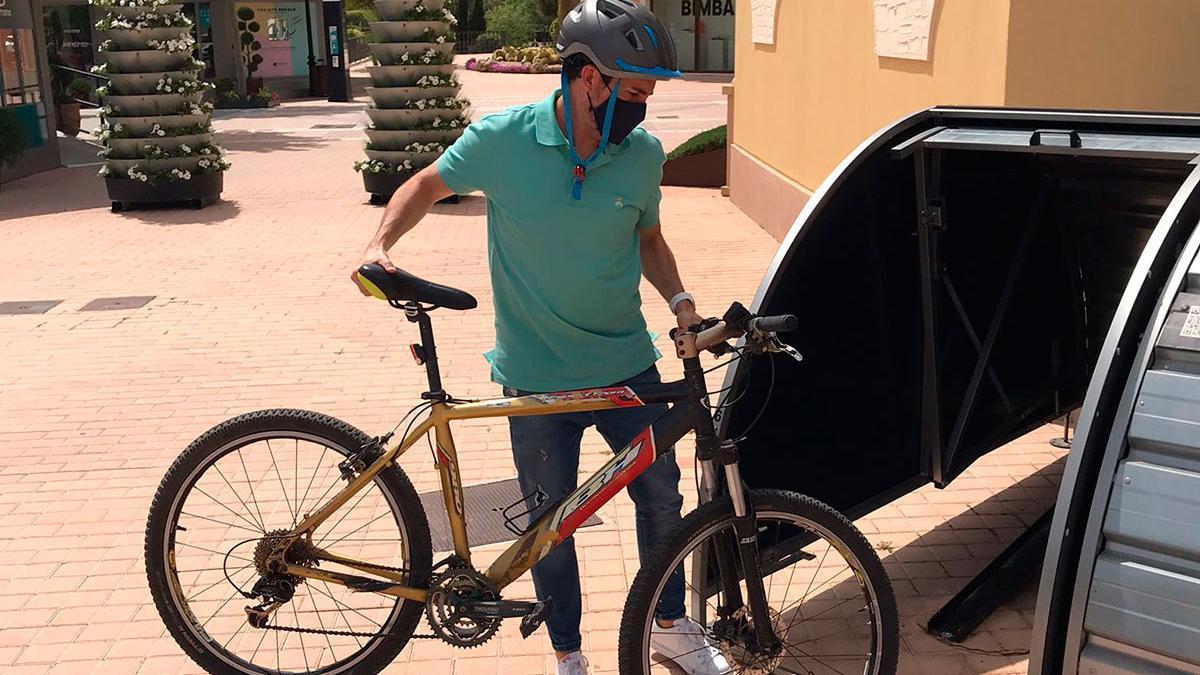 Un empleado aparca su bicicleta en los contenedores inteligentes para bicicletas, gestionares a través de una APP