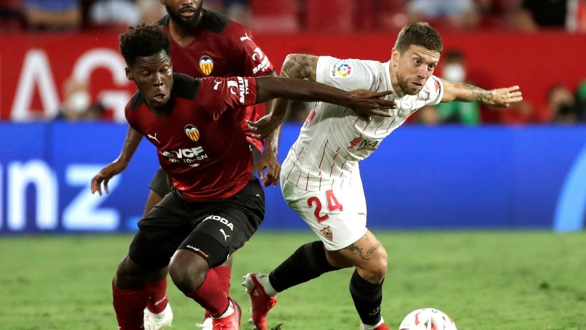 """El centrocampista del Sevilla """"Papu"""" Gómez (d) pelea un balón con Yunus Musah (i), del Valencia."""