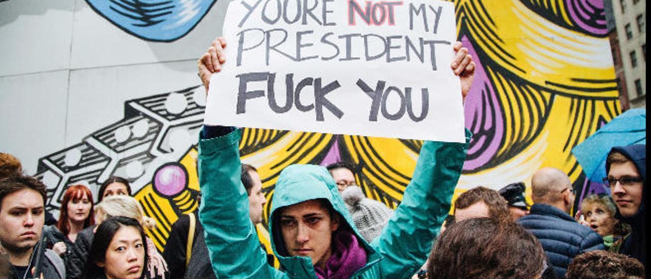 A la izquierda, una imagen de Clinton 'por los suelos'. Arriba, manifestantes en la Torre Trump de Nueva York.