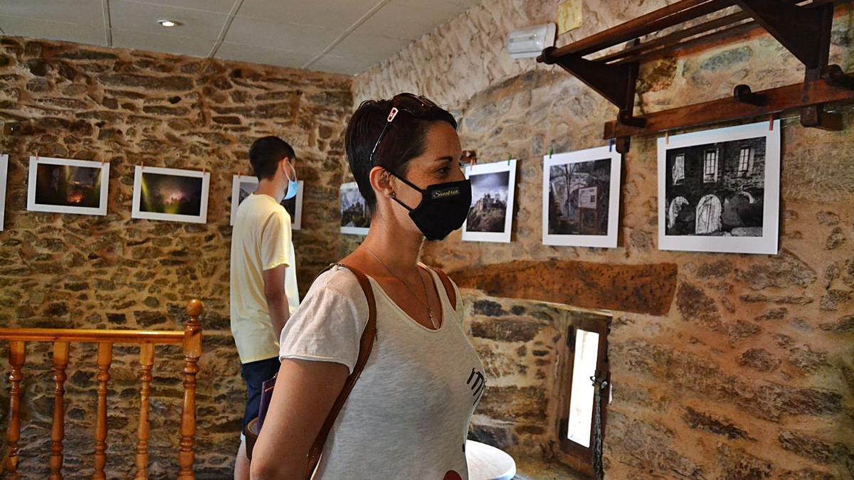 Dos personas siguen la muestra fotográfica en El Puente. | A. S.