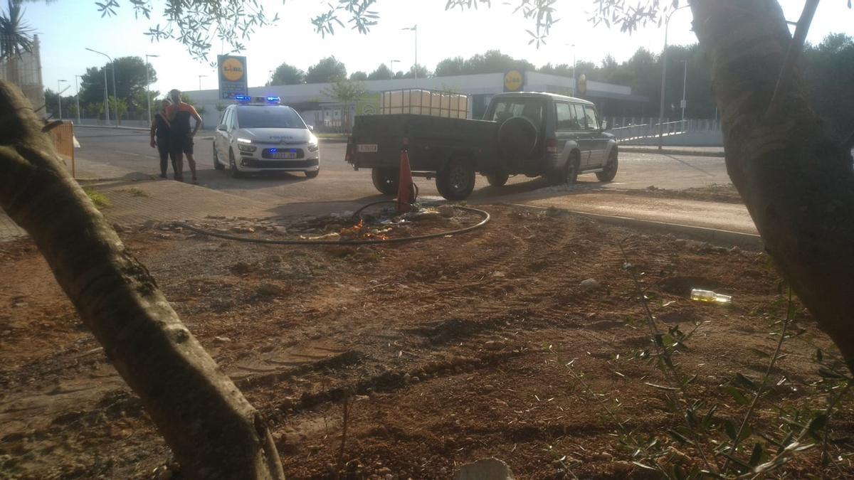 Agentes de Policía, junto al remolque que trasladaba los bidones de agua.