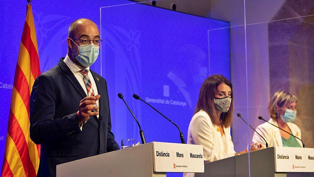 El conseller de Interior, Miquel Buch (izq.), al anunciar ayer las nuevas restricciones.