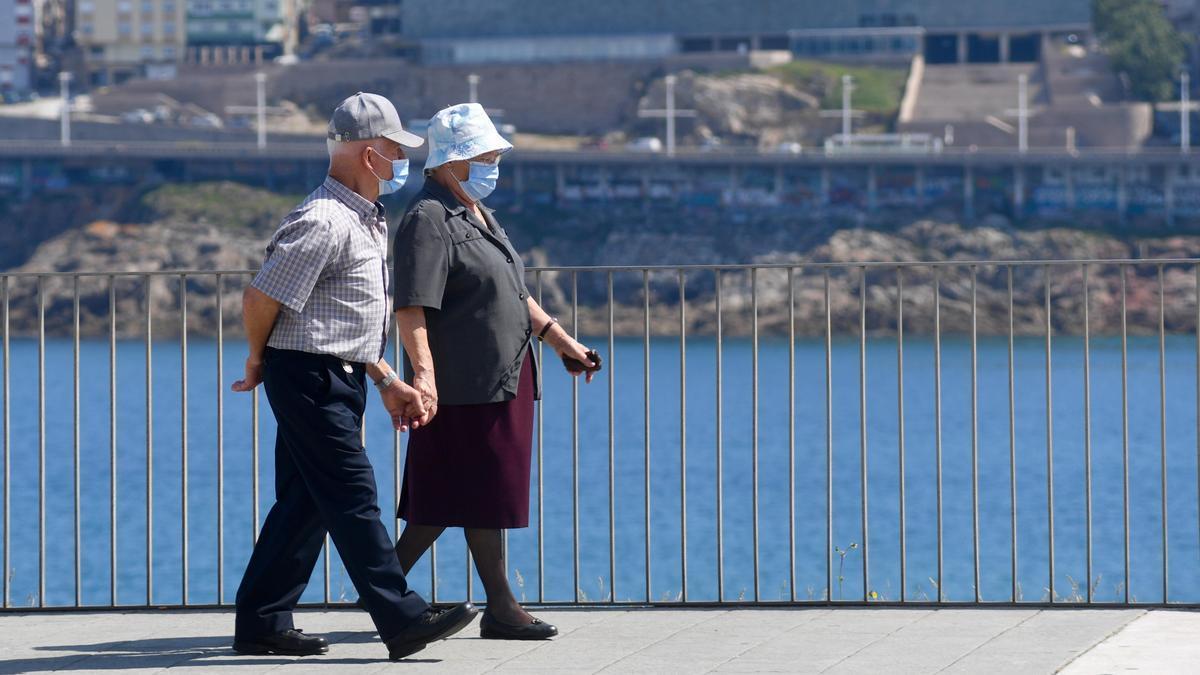 Una pareja pasea con sus mascarillas por A Coruña.