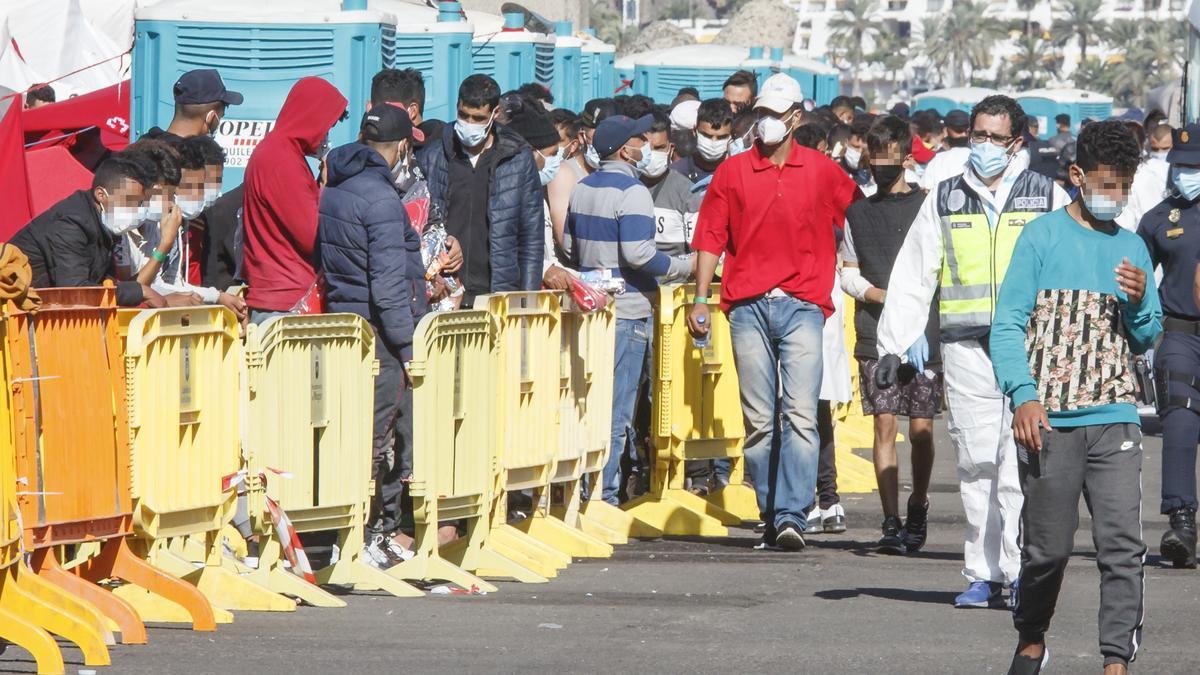 Varios inmigrantes hacen cola en el Muelle de Arguineguín, en Gran Canaria.
