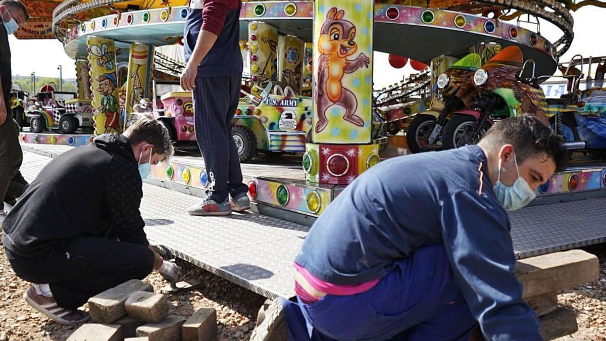 Varios trabajadores inician el montaje de las atracciones. | Jose Luis Fernández