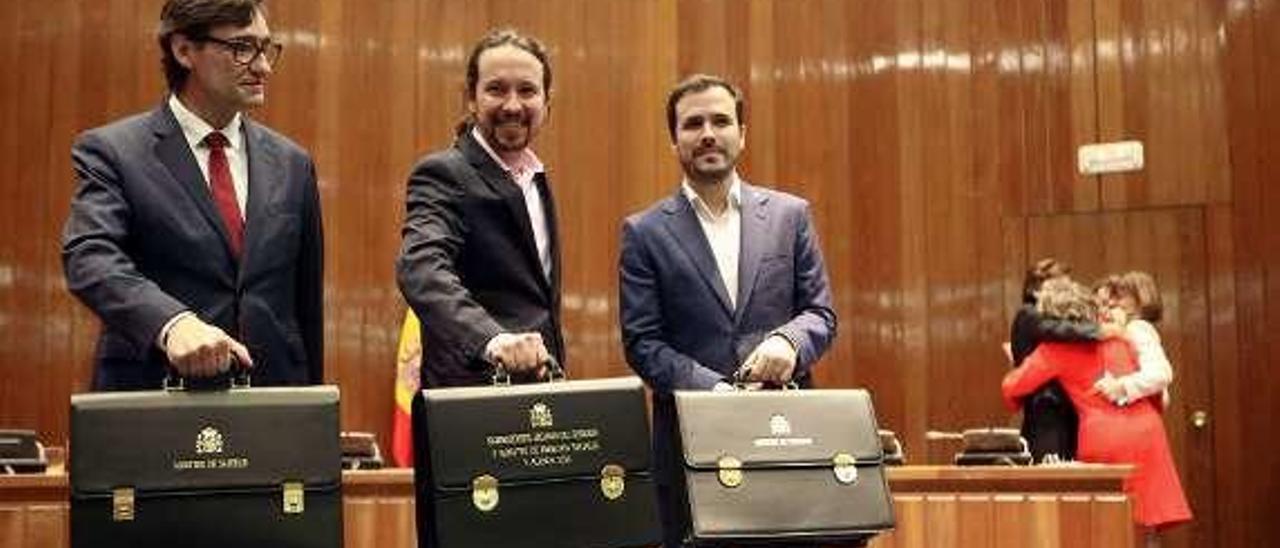 Illa, Iglesias y Garzón, con sus carteras; al fondo, de rojo y despidiéndose, Luisa Carcedo.
